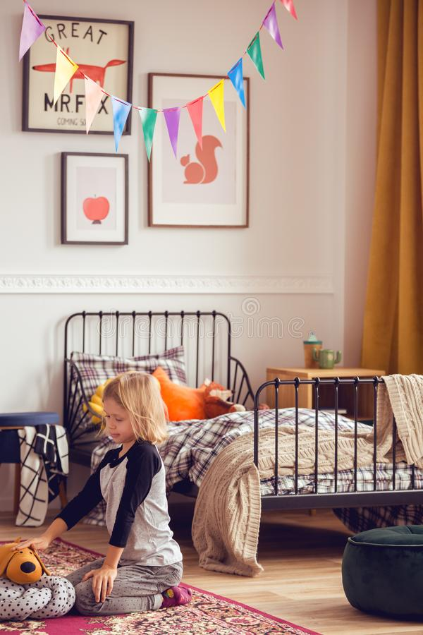 Blonde kid playing with toys in vintage styled unisex bedroom royalty free stock image