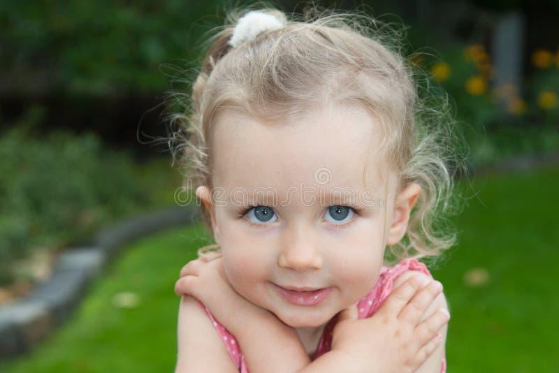 blonde Kindermädchenaufstellung im Freien mit blauen Augen stockfotografie