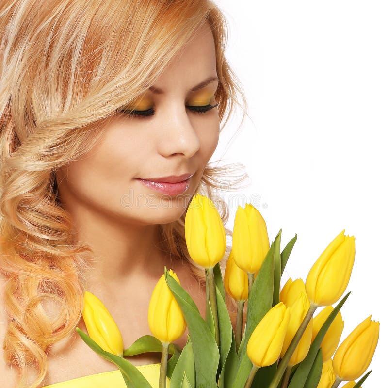 Blonde lächelnde Frau mit den gelben Tulpen, lokalisiert lizenzfreies stockfoto