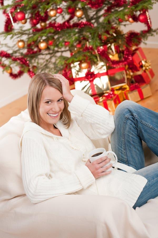 Blonde lächelnde Frau vor Weihnachtsbaum stockfotos