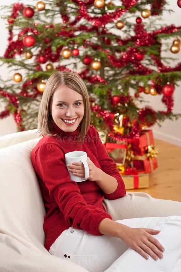 Blonde lächelnde Frau vor Weihnachtsbaum lizenzfreie stockbilder