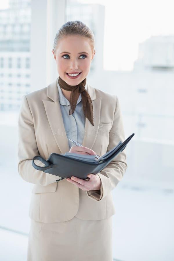 Blonde lächelnde Geschäftsfrau, die ein Tagebuch hält stockbild