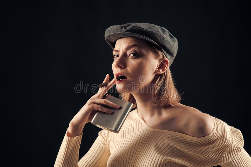 Blonde lady looks like suspicious detective. Detective concept. Girl thinking about investigation, holds flask and. Smoking cigar, copy space. Woman on stock photography
