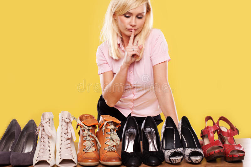 Blonde lady with a passion for shoes stock images