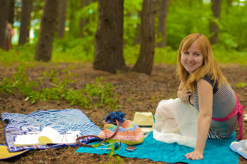 A blonde lady is in a pine forest stock photo