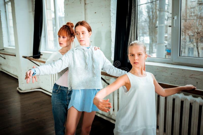 Blonde langharige tiener die in witte kleding geconcentreerd kijken royalty-vrije stock foto