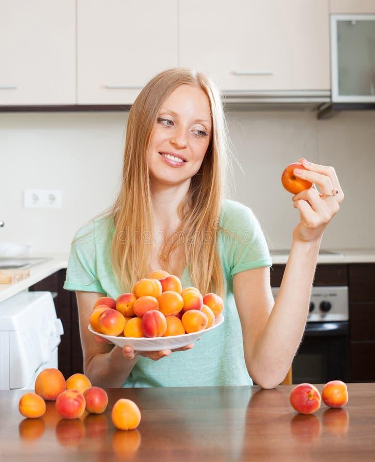 Blonde langharige vrouw die abrikozen in huiskeuken eten stock foto