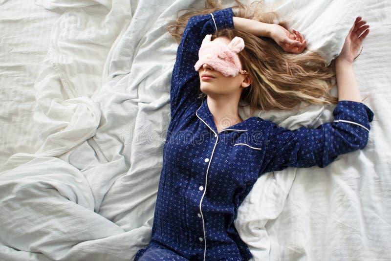 Blonde lindo en su cama en pijamas y la máscara azules del sueño, visión superior foto de archivo