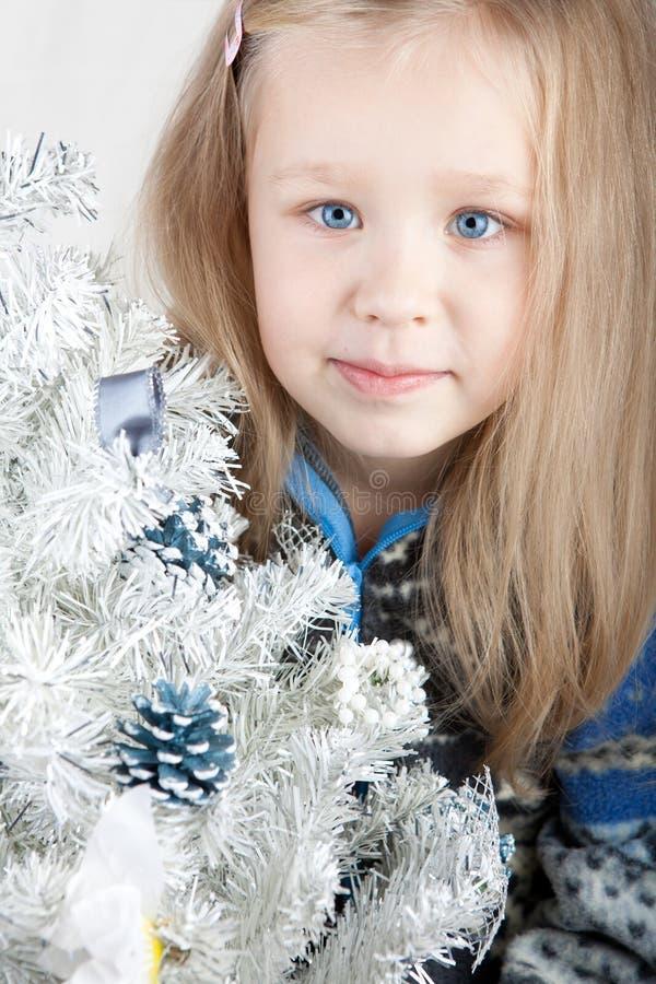 Blonde Lindo En Un Suéter Al Lado De Una Navidad Blanca Foto de archivo
