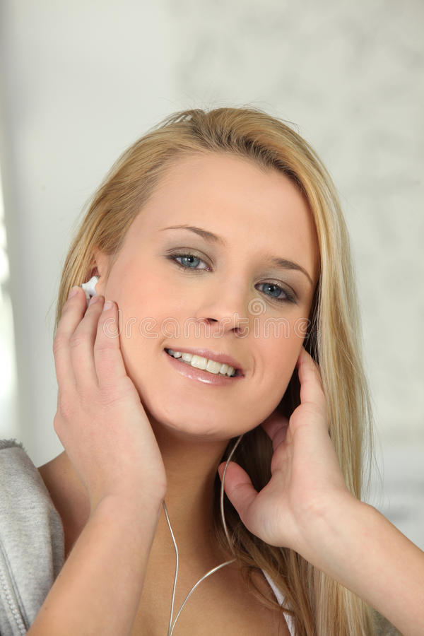 Download Blonde listening to music stock photo. Image of device - 35522474