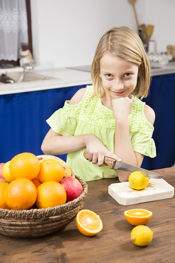 Blonde little gir in kitchen make a juice royalty free stock images