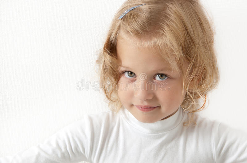 Blonde little girl dressed in white royalty free stock photography