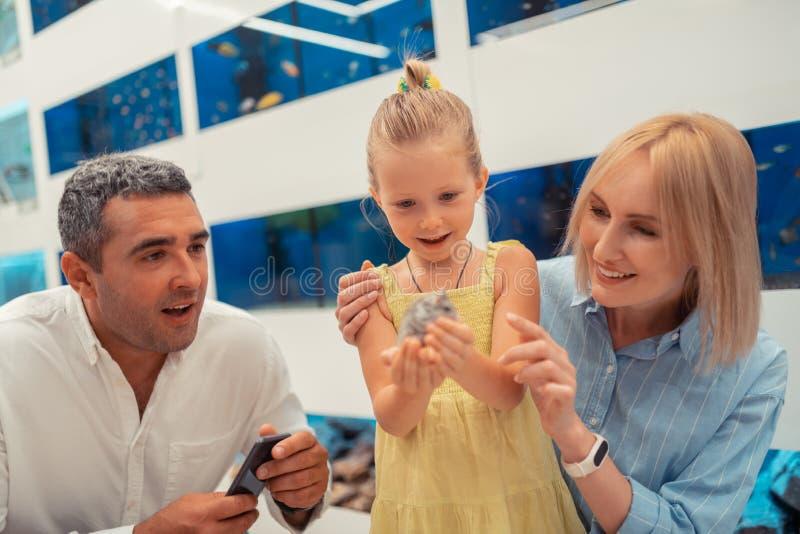 Blonde little girl feeling amazing while holding hamster stock photos