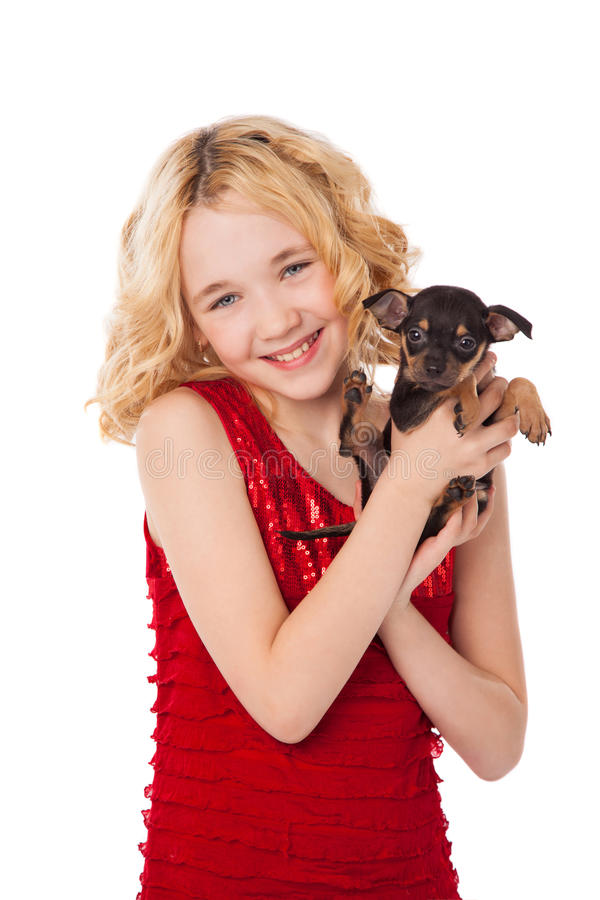 Blonde little girl holding puppy wearing red dress. Beautiful blonde little girl holding puppy wearing red dress royalty free stock photo