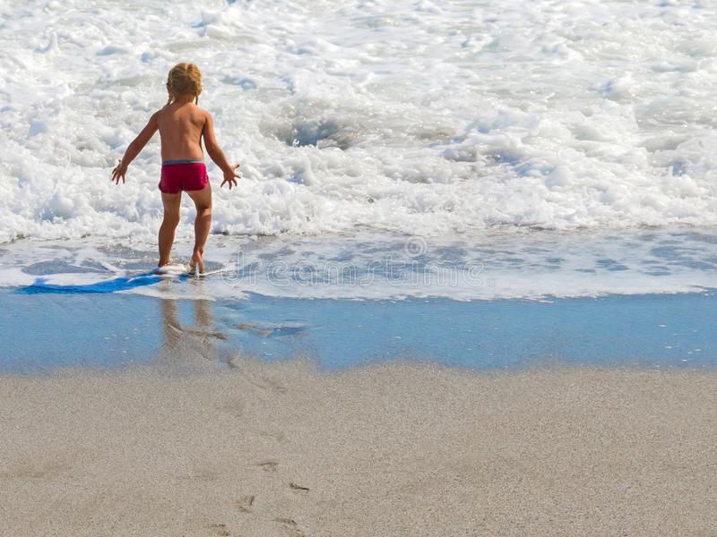 Blonde little girl with pigtails in the beach stock photography