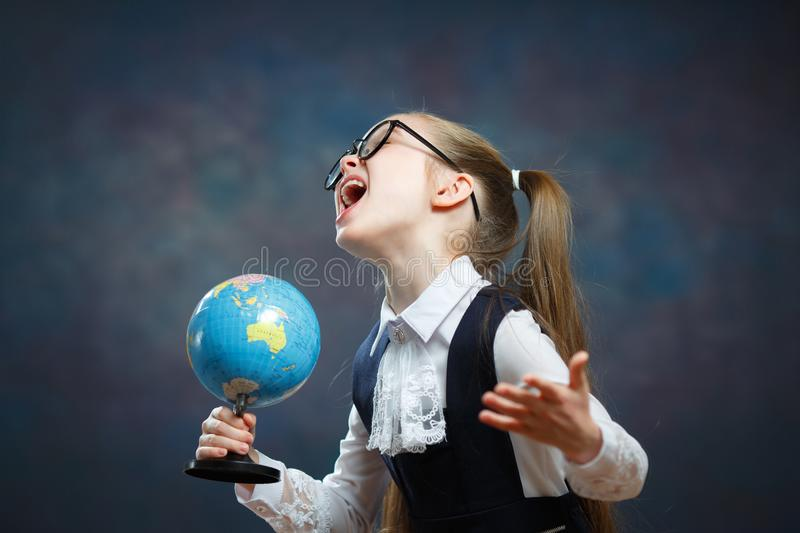 Blonde Little Schoolgirl Hold World Globe in Hand. Female Junior Student Start to Study Geography. Pretty Girl with two Long Ponytail in School Uniform Look at stock image