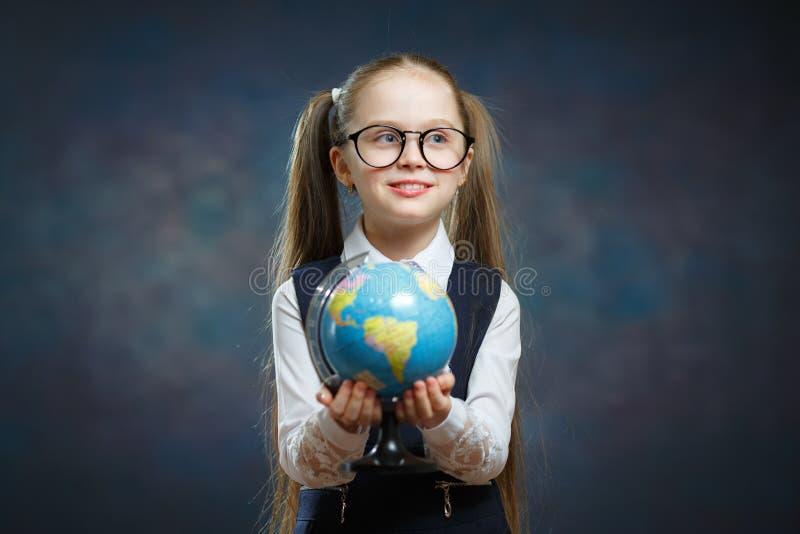 Blonde Little Schoolgirl Hold World Globe in Hand stock images