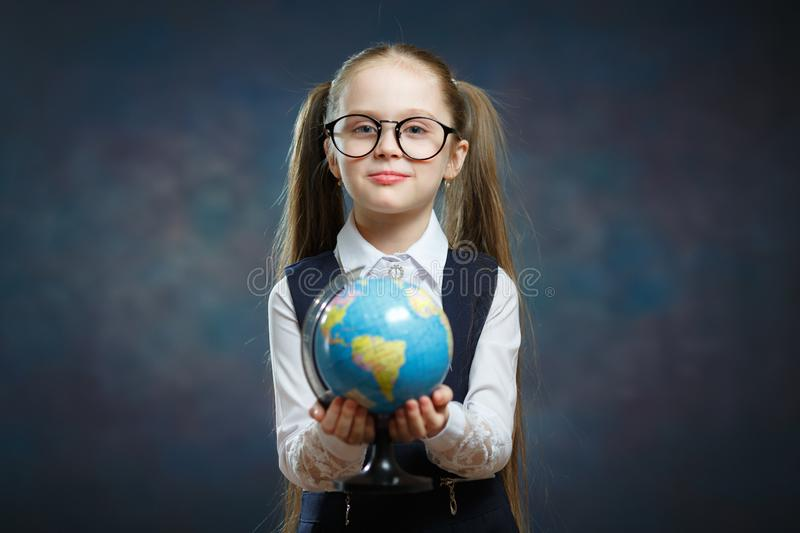 Blonde Little Schoolgirl Hold World Globe in Hand. Female Junior Student Start to Study Geography. Pretty Girl with two Long Ponytail in School Uniform Look at royalty free stock photos