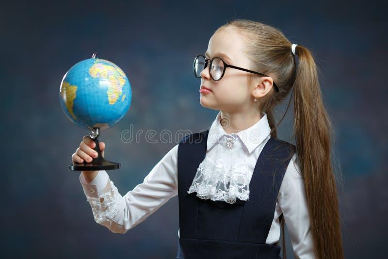 Blonde Little Schoolgirl Hold World Globe in Hand royalty free stock photo