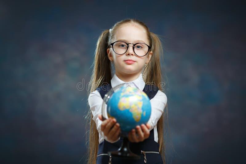 Blonde Little Schoolgirl Hold World Globe in Hand stock photos