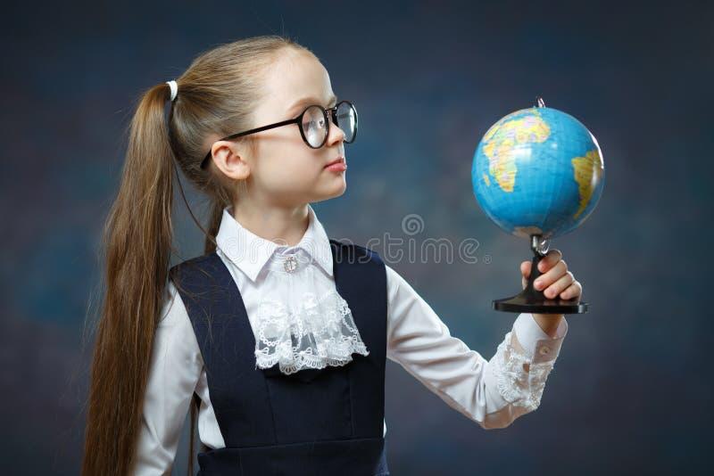 Blonde Little Schoolgirl Hold World Globe in Hand royalty free stock image