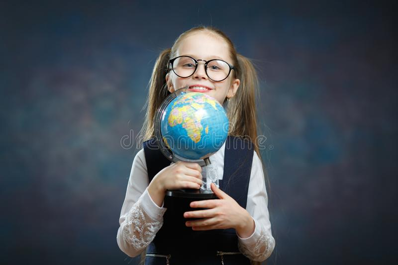 Blonde Little Schoolgirl Hold World Globe in Hand royalty free stock photography