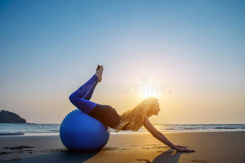 Blonde with long hair makes Pilates on the beach during sunset against the sea. Young flexible happy woman doing fitness exercises. On blue ball in the light of royalty free stock photo