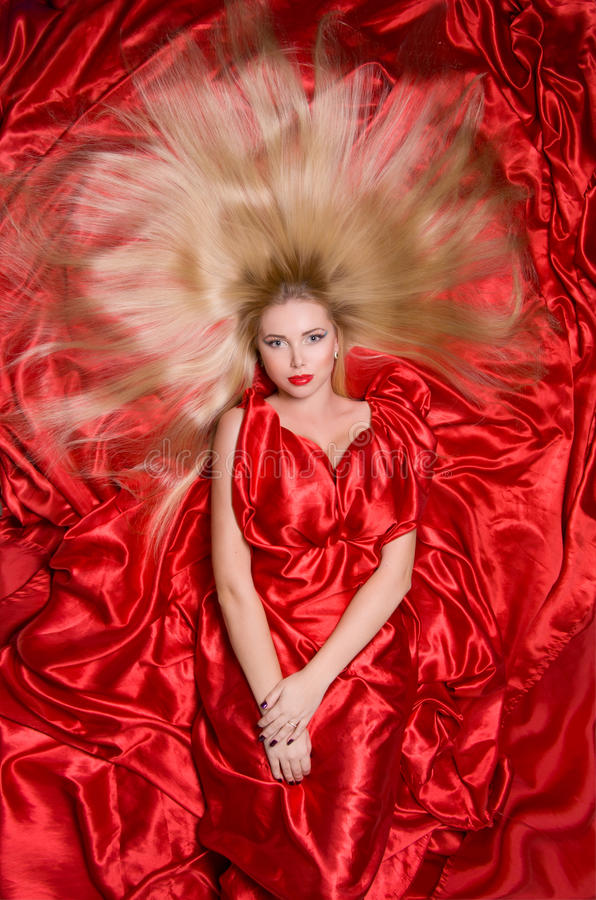 Blonde with long hair on red fabric stock photo