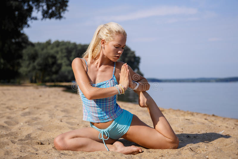 Blonde long haired girl in a blue suit is stretching and doing yoga on a lovely beach in sunlight of the rising sun. Blonde long haired girl in a blue suit is stock images
