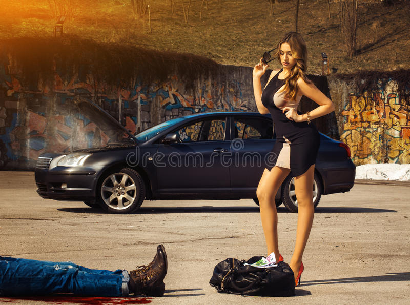 Blonde luxury woman stand over bag full of money amin fuming car. Blonde luxury women stand over bag full of money amin fuming car outdoors stock photos