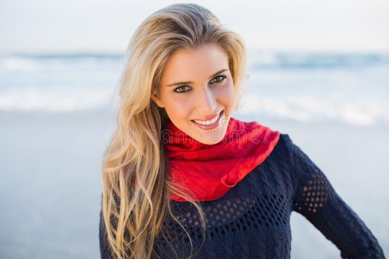Blonde magnífico alegre con la presentación roja de la bufanda fotografía de archivo