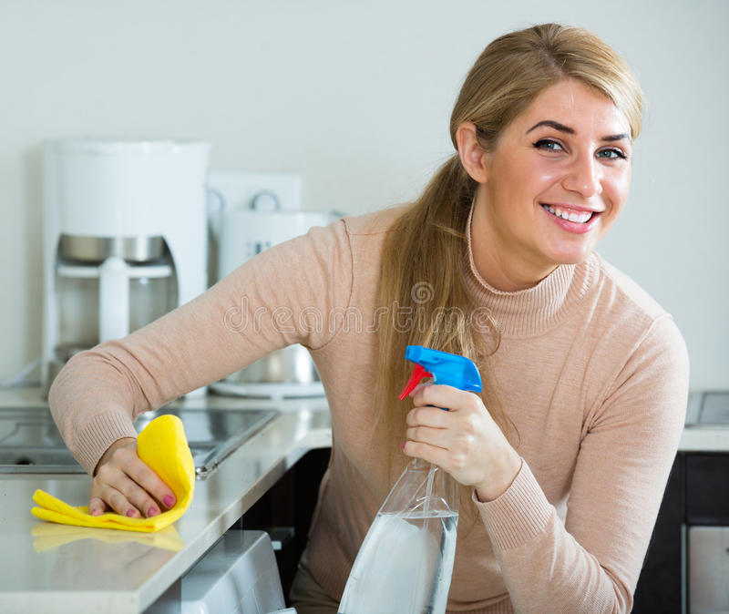 blonde maid cleaning in kitchen stock photo - image of