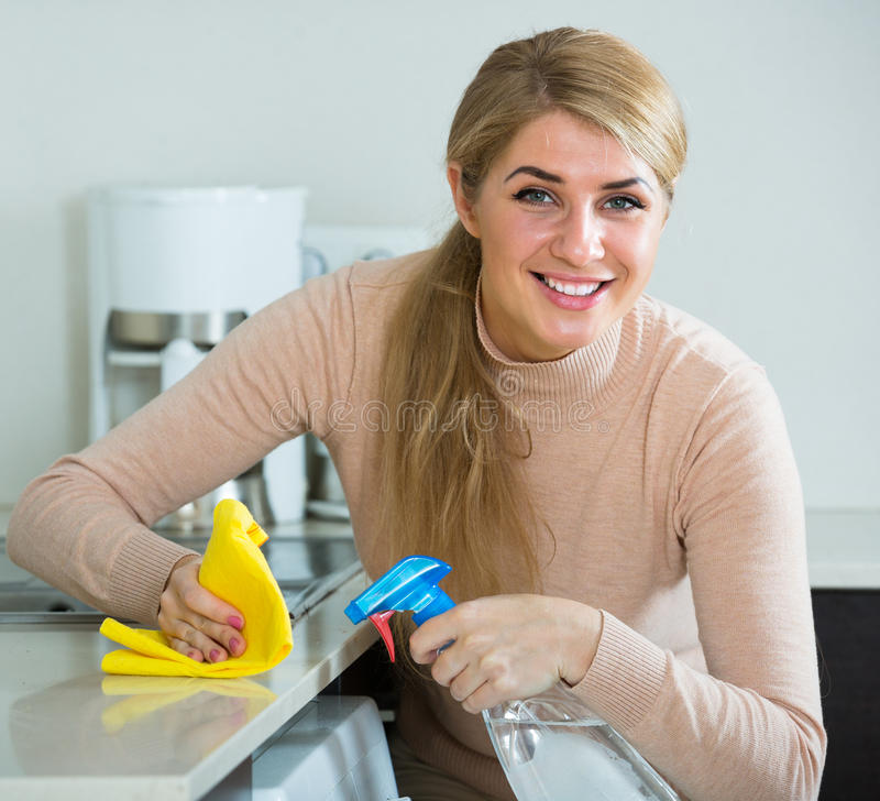 blonde maid cleaning in kitchen stock image - image of