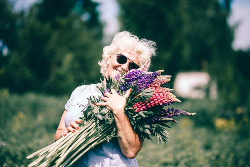 Blonde mature stout woman holding a lupine bouquet on nature background. The concept of beauty and Body Positive. Sunset light stock photography