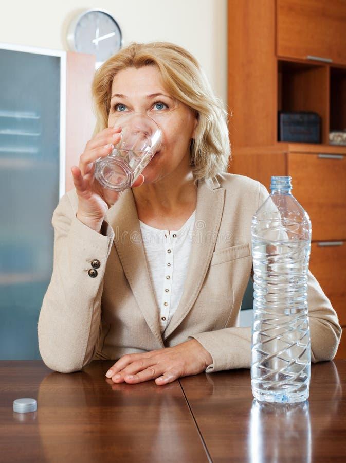 Blonde mature woman drinking water royalty free stock image