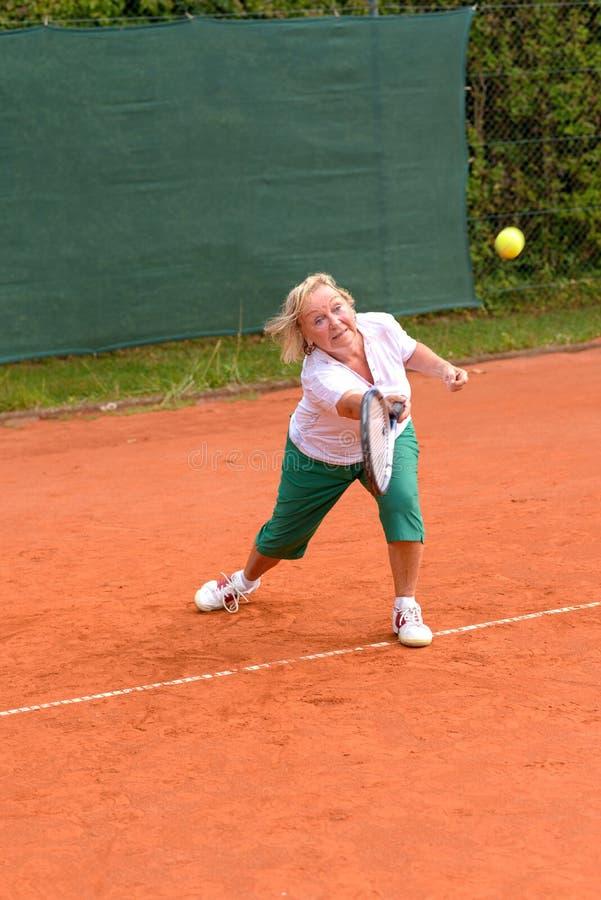 Senior woman playing tennis stock photos