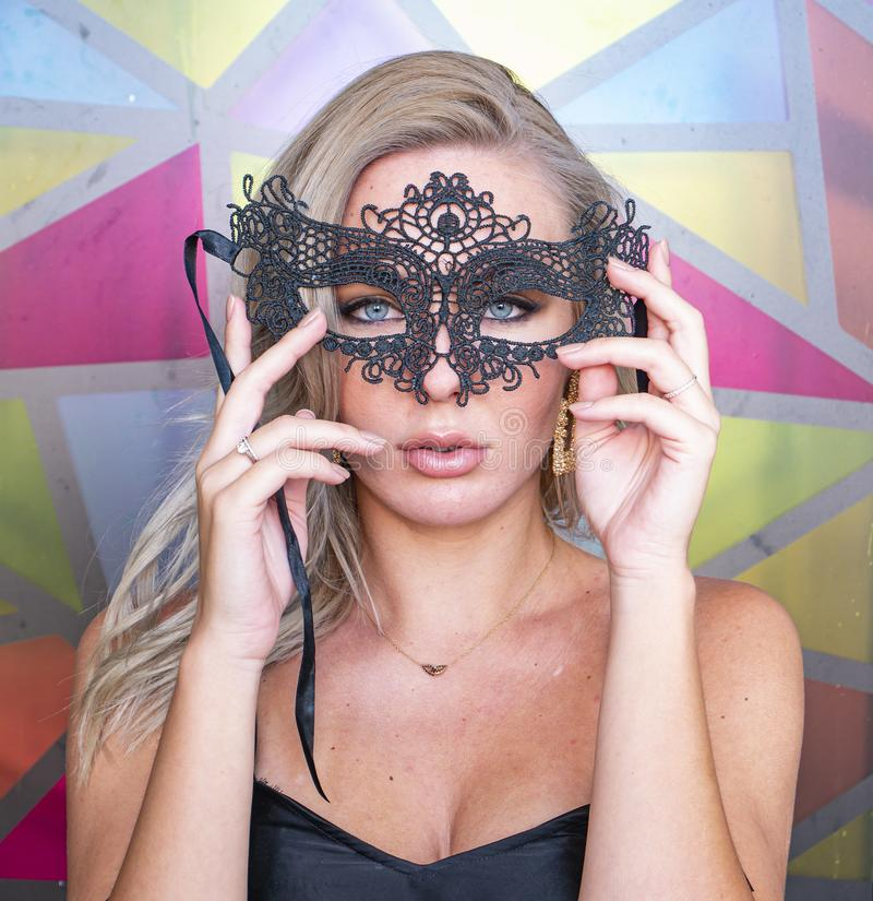 Blonde meisje in een zwart maskerade masker stock afbeeldingen