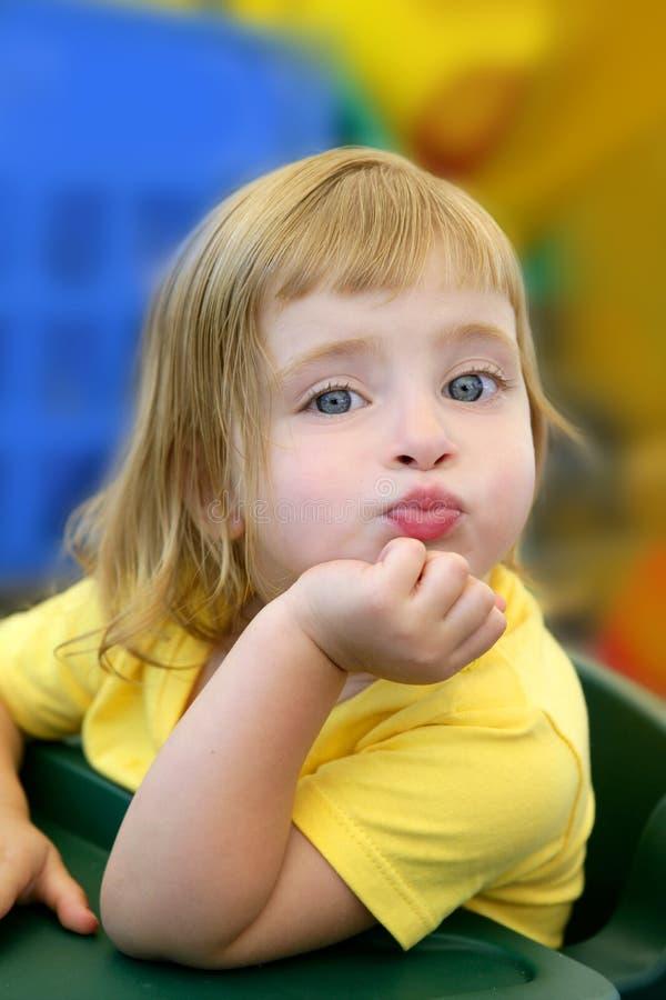 Blonde meisje grappige uitdrukking in haar mond stock foto's