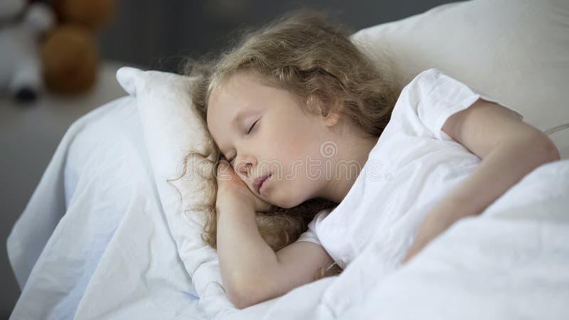 Blonde meisjeslaap in comfortabel bed thuis, kalme rust voor goede gezondheid stock foto