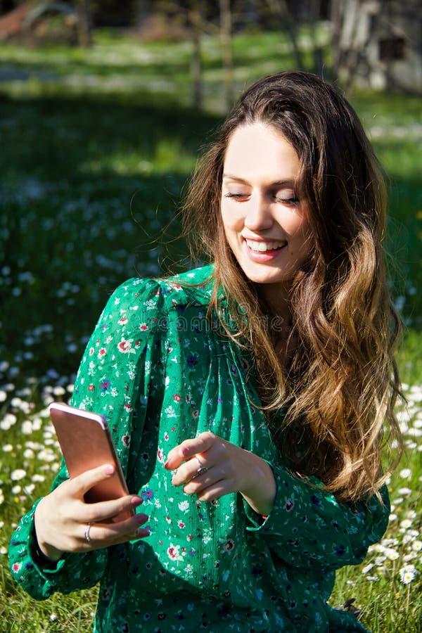 Blonde meisjeszitting in de tuin die mobiele telefoon met behulp van royalty-vrije stock fotografie