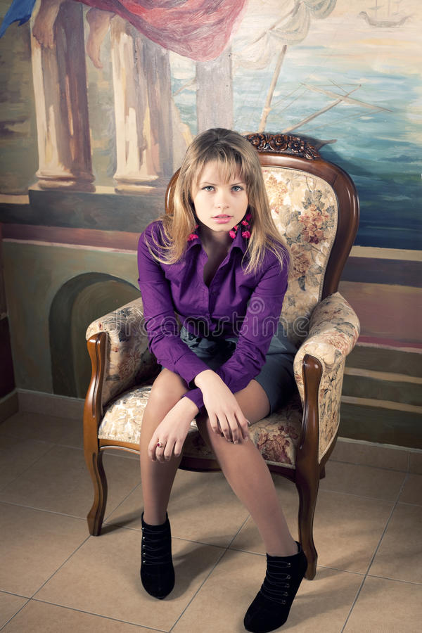Blonde meisjeszitting op een luxeleunstoel royalty-vrije stock afbeeldingen