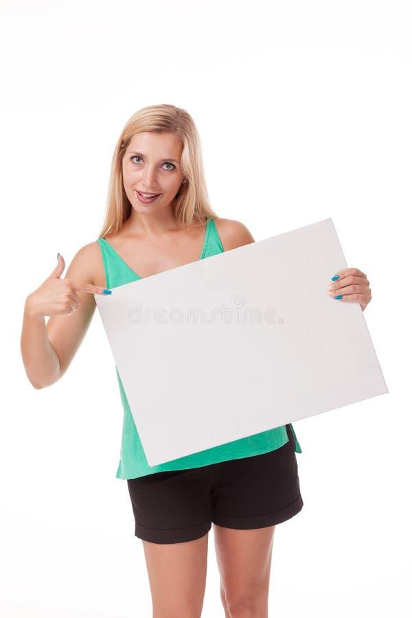 Blonde met het lange haar stellen met witte plaat Zet een embleem, reclame Foto op een witte achtergrond voor reclame stock foto's
