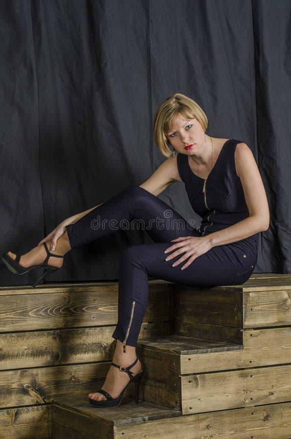 Blonde met kort haar in blauwe overall met kantkokers en sandals met hoge hielen royalty-vrije stock afbeeldingen
