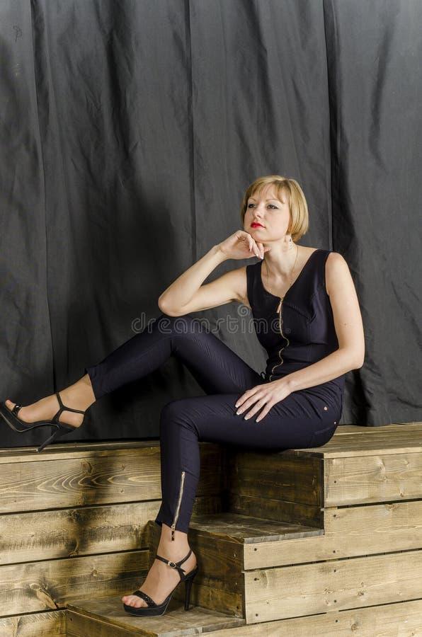 Blonde met kort haar in blauwe overall met kantkokers en sandals met hoge hielen stock foto