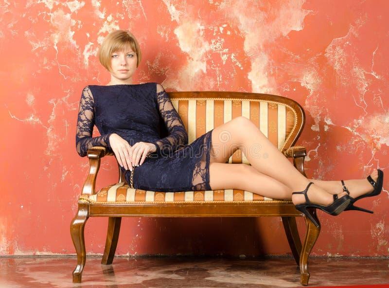 Blonde met kort haar in blauwe overall met kantkokers en sandals met hoge hielen stock fotografie