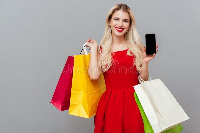 Blonde met telefoon en zakken royalty-vrije stock afbeelding