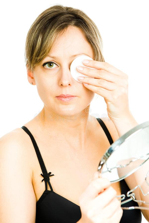 Blonde mid aged woman cleaning face with cotton pad - skin care at any age - covering one eye royalty free stock image