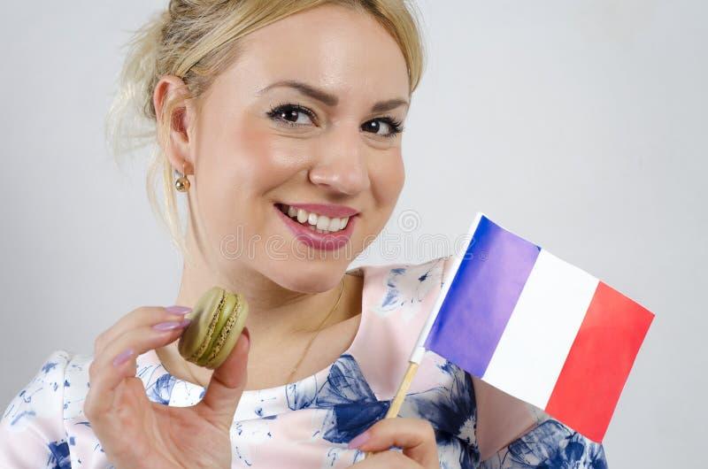 Blonde mignonne tenant le macaron simple et le drapeau français photos libres de droits