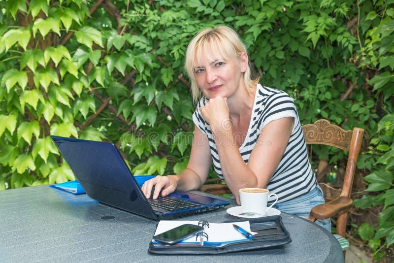 Blonde mittlere Greisin sitzt Büro im im Freien stockbilder