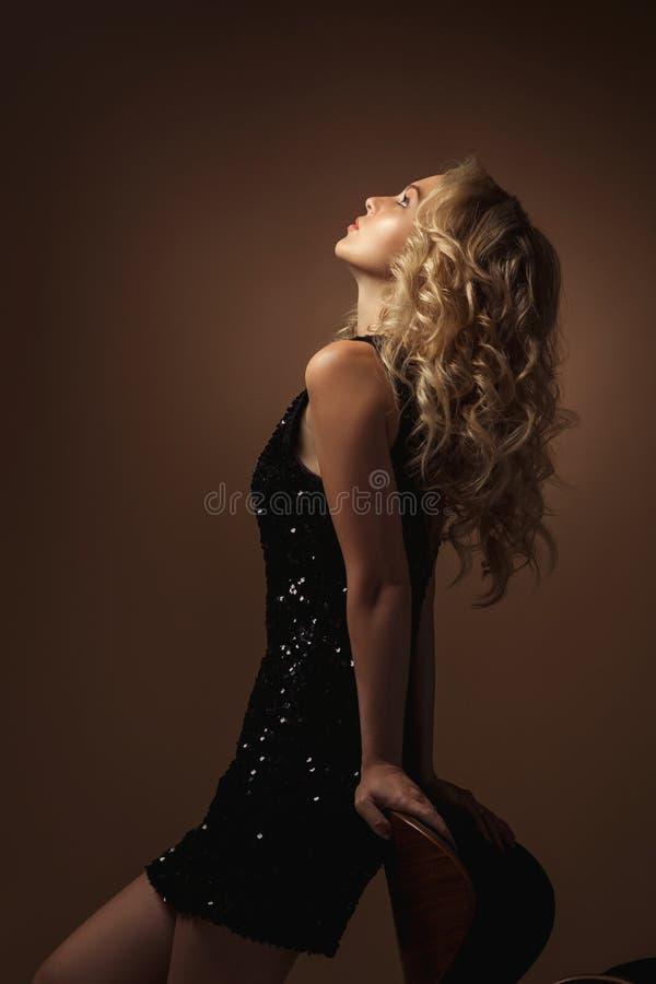 Blonde Modefrau im herrlichen schwarzen Kleid stockfotos